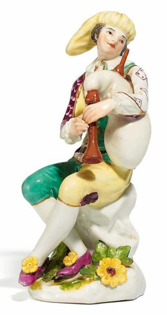 THE SEATED HARLEQUIN WITH YELLOW CAP AND BAGPIPES. Meissen. At the end of 18. Century.