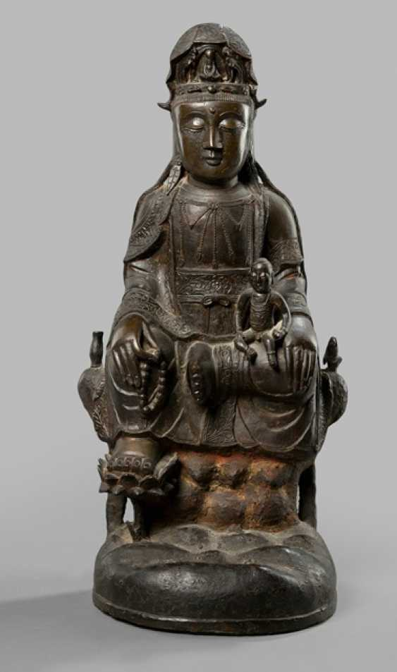 Bronze of a Guanyin on a high cliff with a boy sitting - photo 1