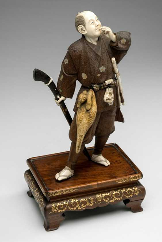 Okimono of a standing duck hunter in wood with Details in ivory - photo 1