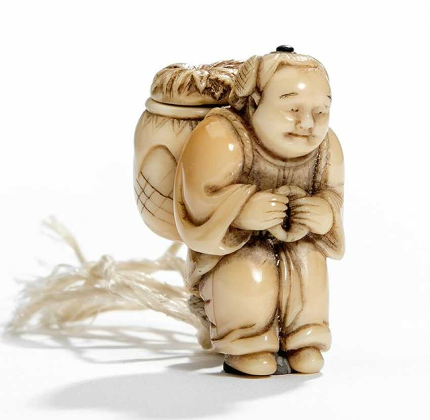 Netsuke of a farmer from marine ivory, carrying a basket on his back - photo 1