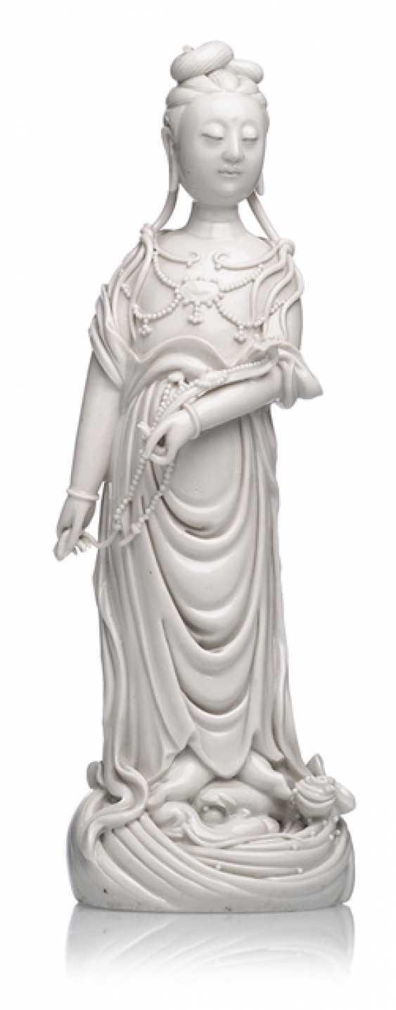 Dehua figure of standing Guanyin on a wave base with Ruyi - photo 1