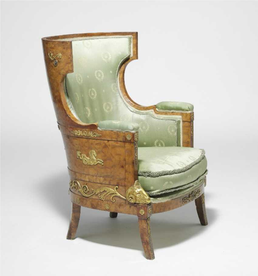"A Russian flamed birch wood and gilt bronze mounted ""bergère à oreilles"", curved back and seat with cushion. Early 19th century. H. 100 cm. W. 72 cm. D. 74 cm. - photo 1"