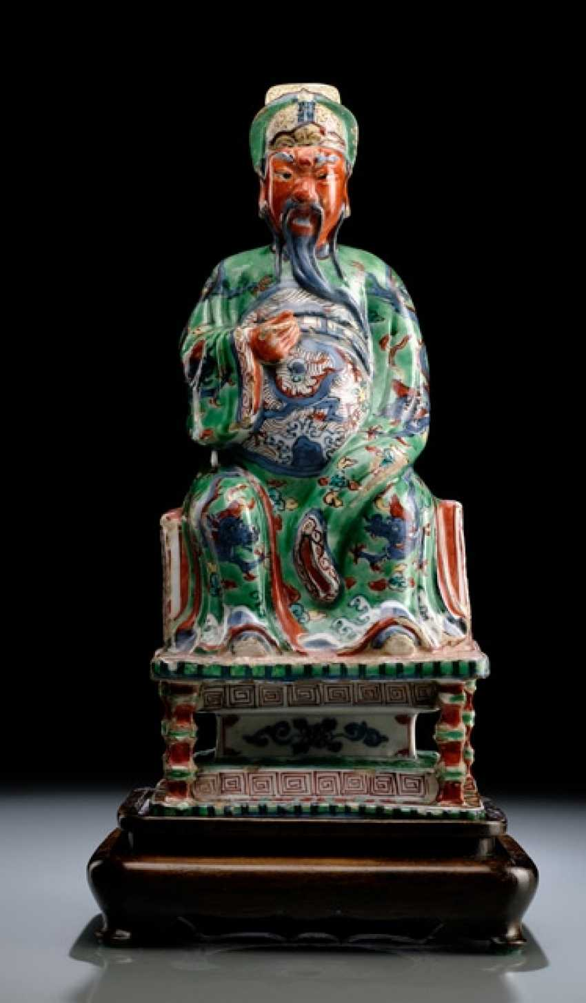 A VERY RARE WUCAI FIGURE OF GUANDI ON A THRONE WITH WOOD