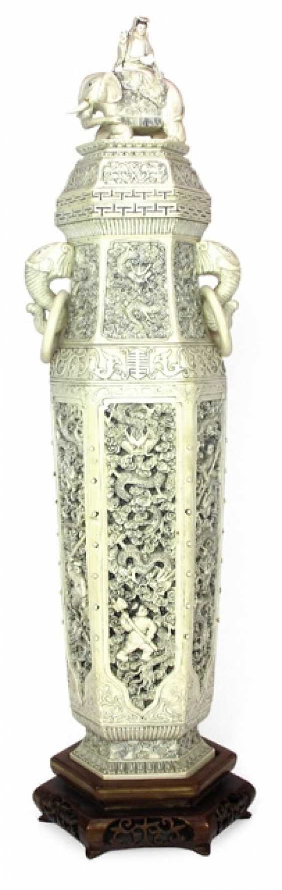 Large and richly carved ivory lidded vase on wood stand