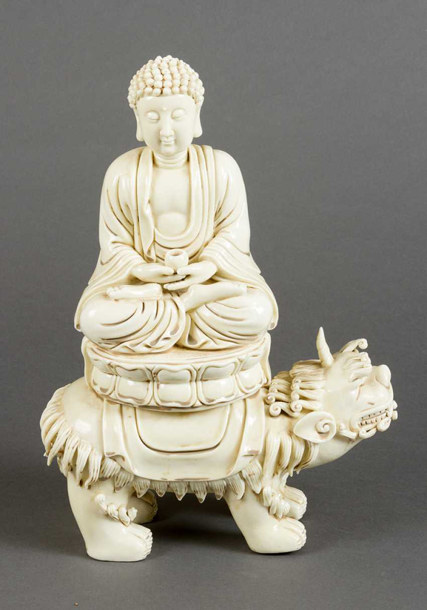 Blanc-de-Chine porcelain sculpture of Buddha sitting in lotus shaped seat, with a pot for the poor, on a fantastic animal - photo 1