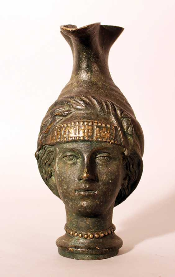 Bronze jug after the ancient, in shape of a female head with long neck as stand and bowed pressed spout - photo 1