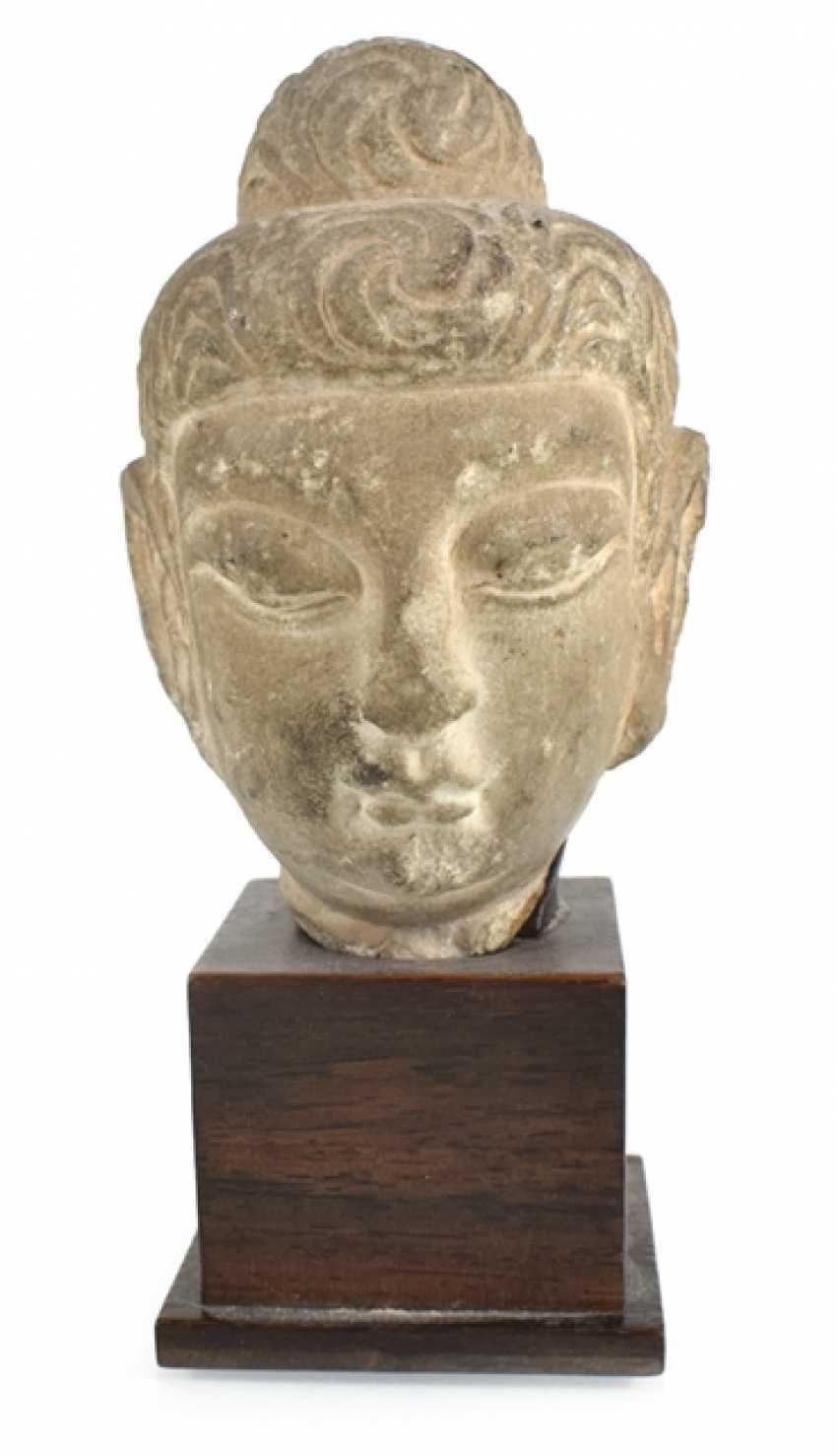 Stone head of Buddha on a wooden base - photo 1