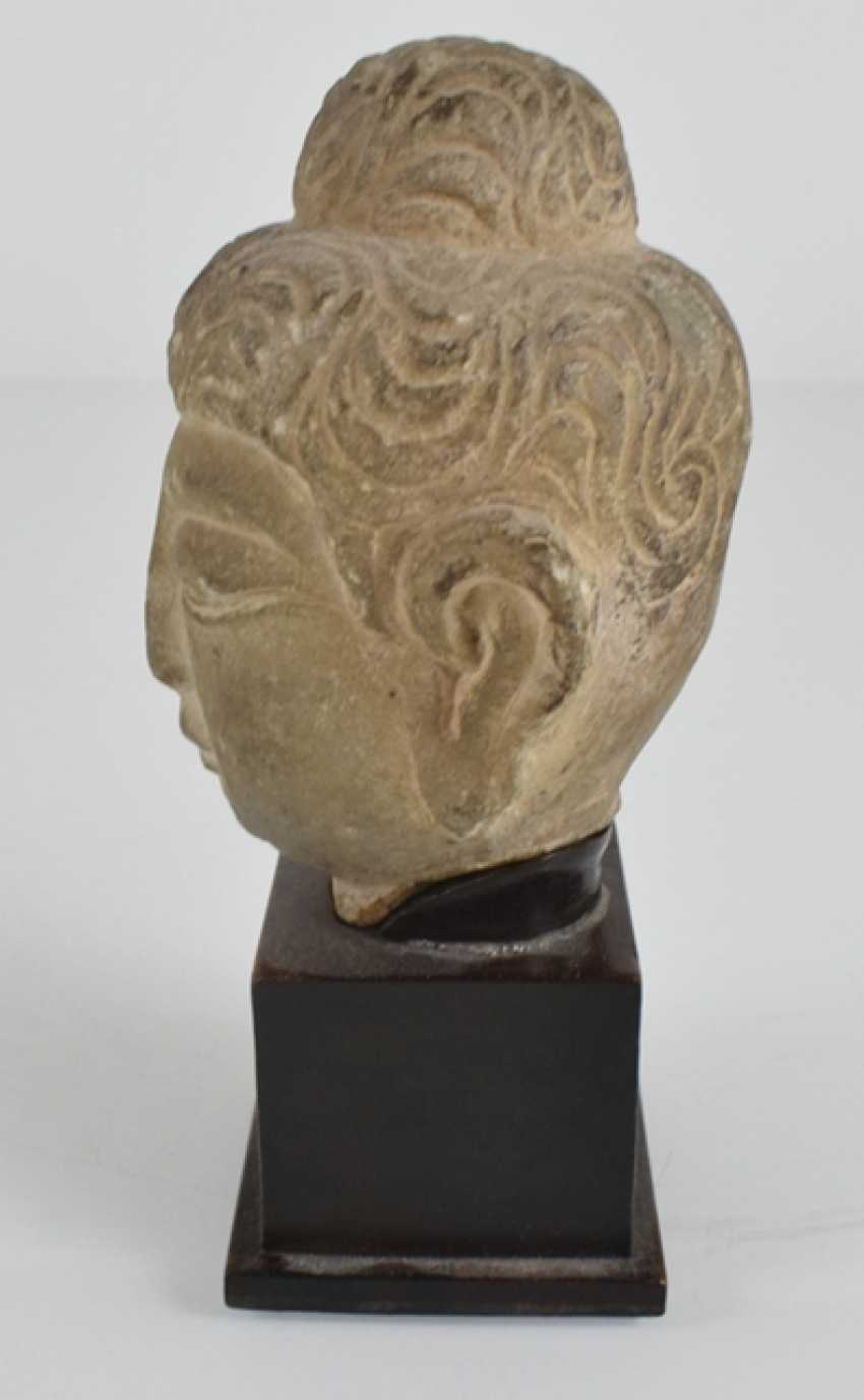 Stone head of Buddha on a wooden base - photo 2