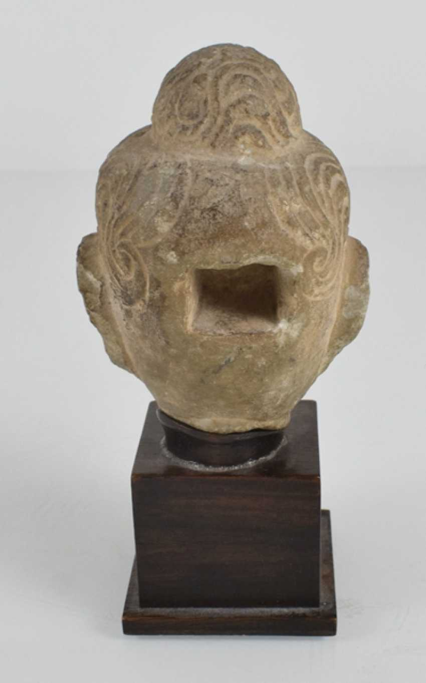 Stone head of Buddha on a wooden base - photo 3