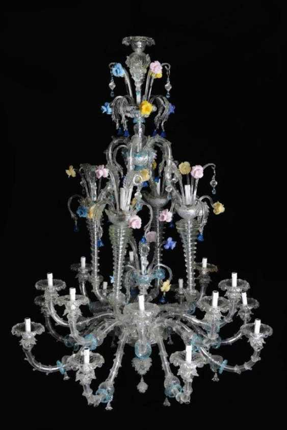 A large Venetian multicoloured and transparent 21 lights Murano glass chandelier with 16 S-shaped branches and spouts, 4 concave spiral columns ending in spouts and with turned connection to the upper central crown - photo 1