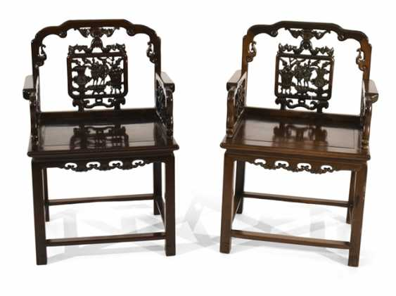 Pair of arm chairs made of hard wood with antique decor sit in the back - photo 1