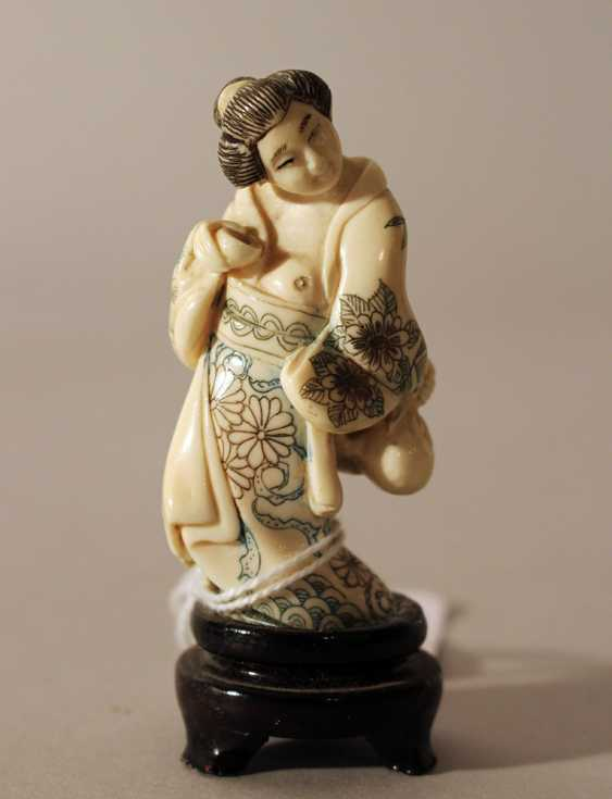 Japanese ivory netsuke showing a woman holding a baker and a bag in traditional dress, partly engraved - photo 1