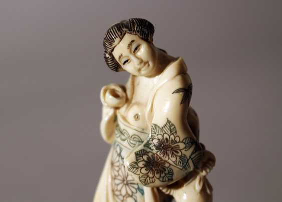 Japanese ivory netsuke showing a woman holding a baker and a bag in traditional dress, partly engraved - photo 3