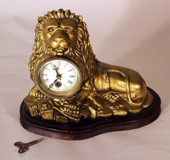 An eye turning clock in shape of a lying lion with enamel dial with Roman numbers - photo 1