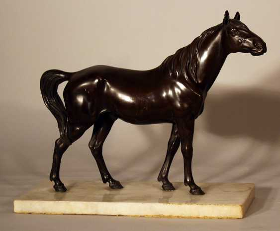 Bronze sculpture of a standing horse looking to the side, on white marble base - photo 1
