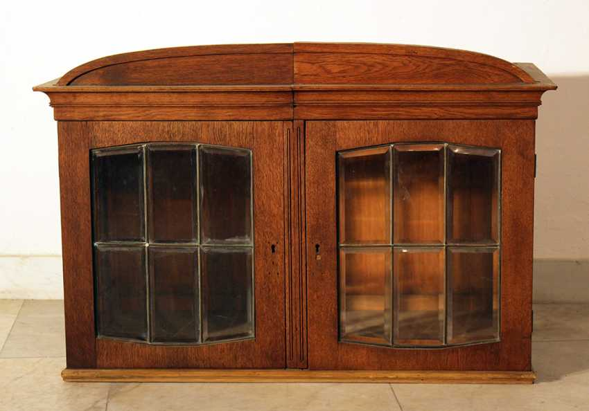 A Jugendstil display cabinet with arched top, two doors and cutted glass windows with bronze grid - photo 1