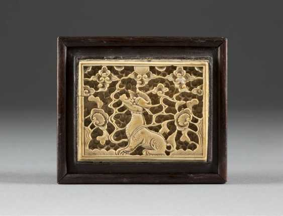 BOX WITH IVORY QILIN DECOR China, around 1900 wood, ivory, carved. 5.3 cm x 9.4 cm x 8.2 cm. Ivory relief on the sliding cover, a smiling Qilin on the shaft seated, the decor of lucky clouds, peony and foliage. Min. best., rest. - photo 1