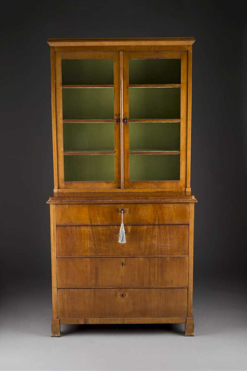 BIEDERMEIER-top vitrine Cabinet, German, around 1815/ 1820. Cherry, veneer. H. 204,5 cm, W 102 cm, d 48 cm. On four block feet of straight, four schübiger base with a two-door, glazed top. Rest., Veneer damage. - photo 1