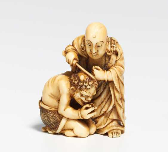 Netsuke of a priest cutting the horn of an oni - photo 2