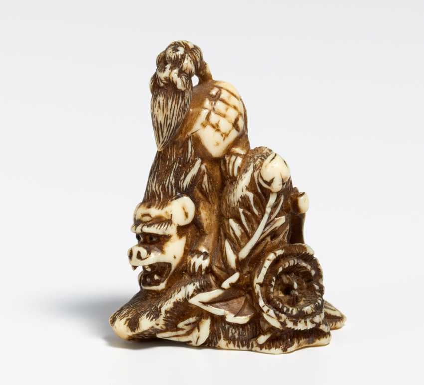 Netsuke: lion on rock with peonies - photo 2
