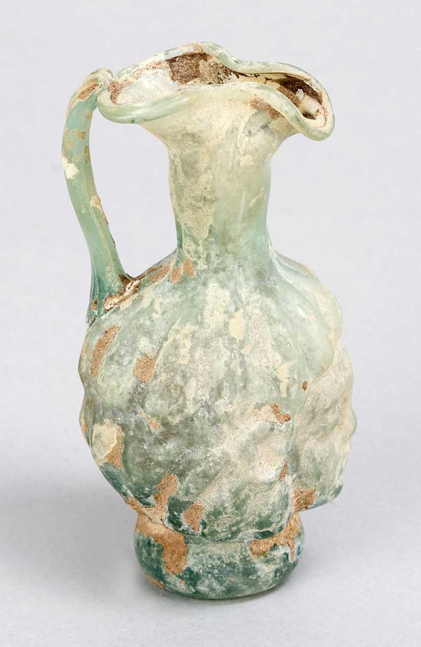 A Roman green glass mold-blown flask