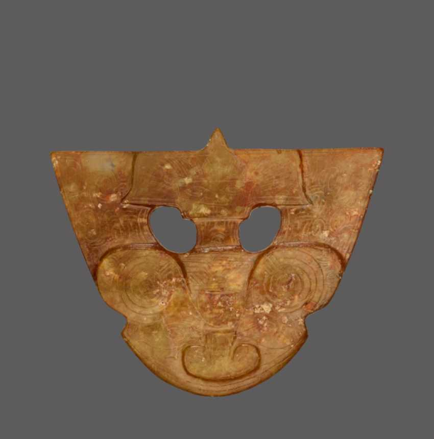 A RARE SMALL ORNAMENTAL PLAQUE MINUTELY CARVED IN OPENWORK AND LOW RELIEF IN THE SHAPE OF A BEING WITH A FEATHERED HEADDRESS AND AN ANIMAL MASK - photo 1