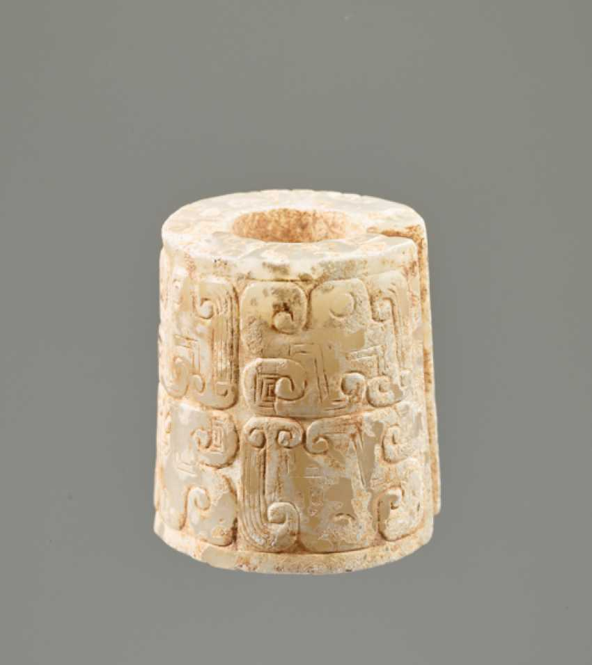 AN INTERESTING THICK EARRING OF THE JUE TYPE IN PARTLY CALCIFIED WHITE JADE DECORATED WITH STYLIZED DRAGON HEADS - photo 1