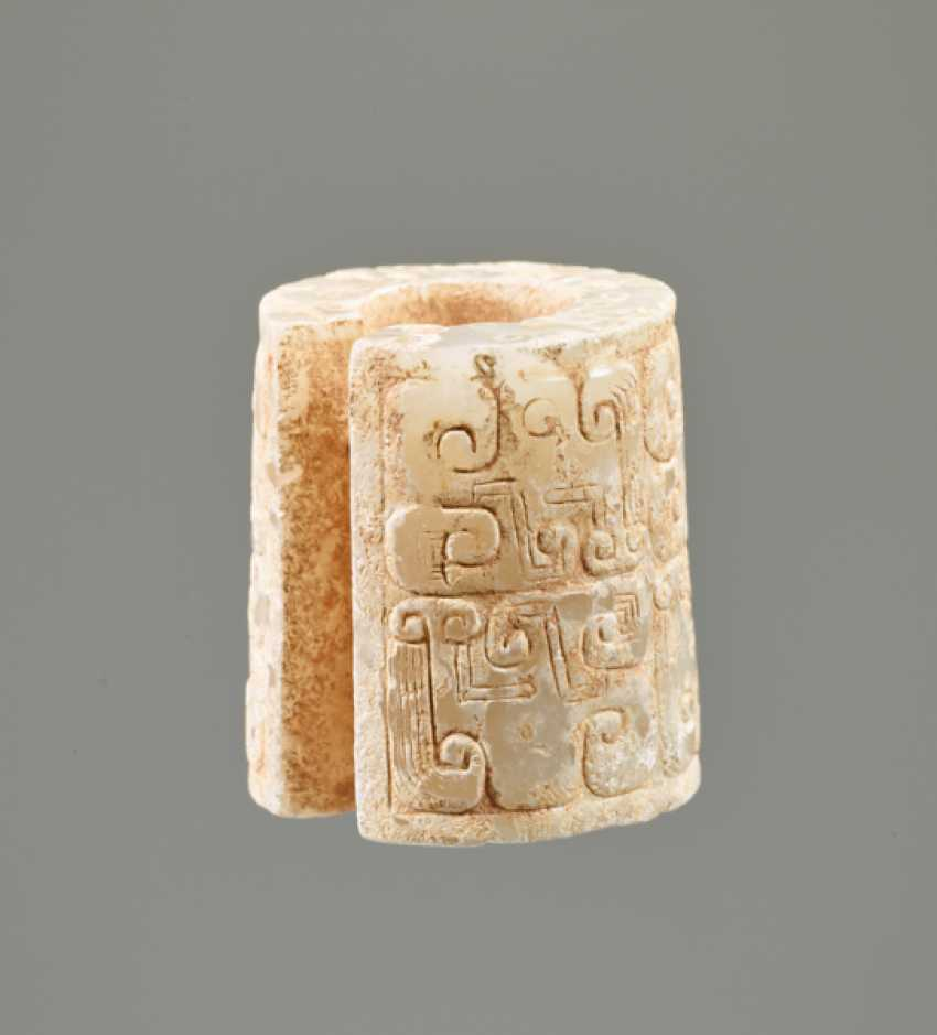 AN INTERESTING THICK EARRING OF THE JUE TYPE IN PARTLY CALCIFIED WHITE JADE DECORATED WITH STYLIZED DRAGON HEADS - photo 2