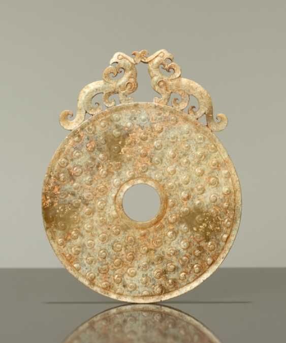 A FINE DISC WITH RAISED CURLS ON THE SURFACE AND A PAIR OF PHEONIXES CARVED ON THE TOP - photo 1