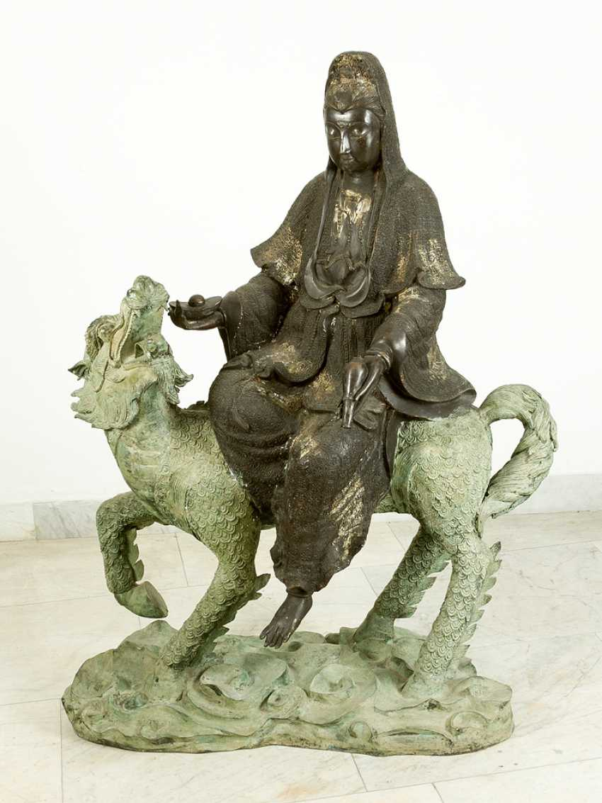 Large Asian bronze group of Guanyin sitting on a fabulous animal, on naturalistic style integrated oval base - photo 1