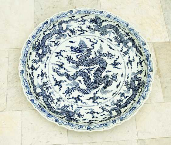Extraordinary and particular large Chinese blue and white porcelain bowl with round shaped border, waved extended high border rim, decorated with a blue painted dragon in the centre with clouds and four dragons on the sides - photo 1