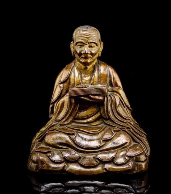 Bronze Arhat Gopaka depicted with a book, seated on a double cushion  - photo 1