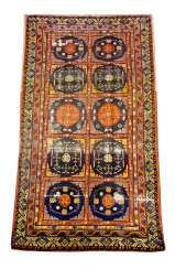 Oriental carpet with ten field decoration bands and rich ornaments in blue red yellow brown and white colours signs of age and use