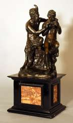 A French bronze group of Satyr and Pan playing the flute and sitting on a rock