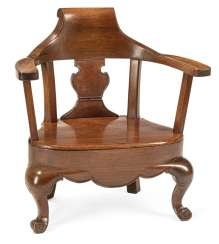 Low chair with wide armrests made of hardwood and the chair in the Form of an officers cap