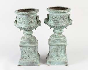 Pair of bronze urn vases on quadratic bases with thinner central and round upper bowl with maidens head on the side