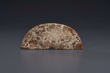 A MOTTLED OPAQUE TAUPE AND AMBER-COLORED JADE PENDANT, HUANG...