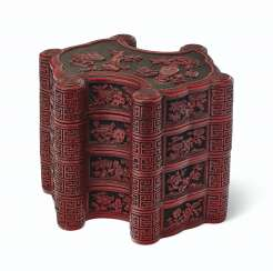 A CARVED RED AND BLACK LACQUER INGOT-FORM THREE-TIERED BOX A...