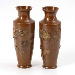 Pair of Japanese brass vases with raised flowers and birds.