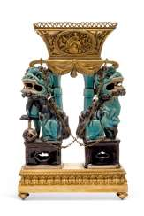 A FRENCH ORMOLU JARDINIERE MOUNTED WITH A PAIR OF CHINESE TURQUOISE AND AUBERGINE-GLAZED PORCELAIN BUDDHIST LIONS