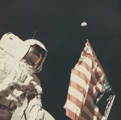 Astronaut Harrison Schmitt with the Earth above the US flag, December 7-19, 1972