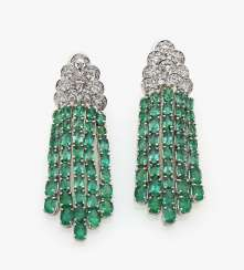 A pair of earrings with diamonds and emeralds