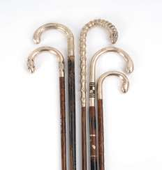 5 walking sticks with silver handles.