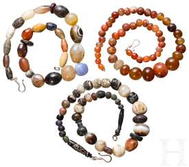 Three necklaces with antique beads, usually made of semi-precious stones, modern threaded