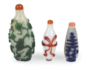 Three Snuffbottles made of glass with a colored Overlay