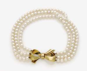 Three-row pearl necklace with bow-shaped gold clasp