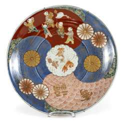 Imari circular plate with a decor of boys and stylized waves