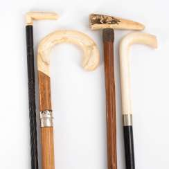 4 walking sticks with ivory knobs.