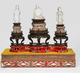 Group of three crystal figures, including Buddha and Guanyin on a wooden base