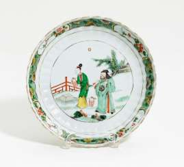 Flower-shaped plate with people in a garden landscape